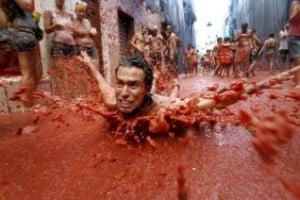 Un joven nada entre los 110.000 kilos de tomate que se han lazado hoy por las calles de la pequeña localidad española de Buñol (Valencia), con motivo de la fiesta de la Tomatina